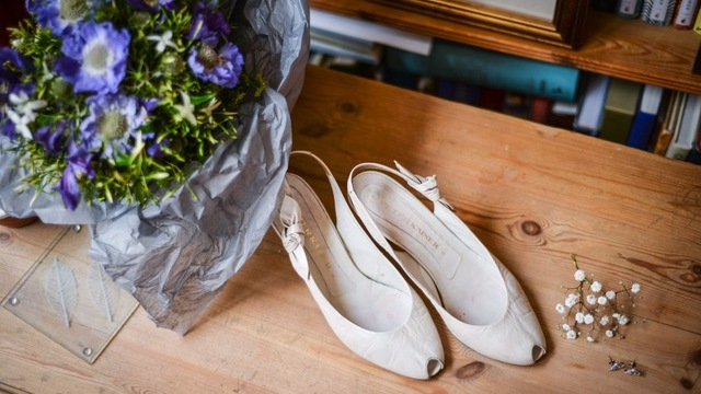 Shoes and purple bouquet on table