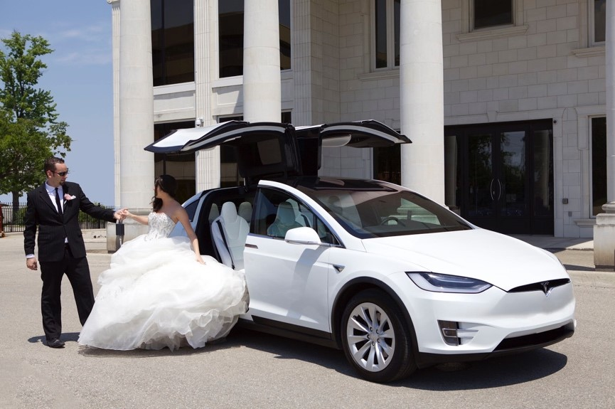 Couple getting out of a Tesla