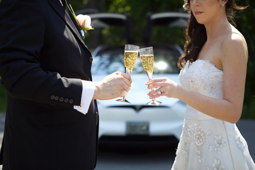 Couple holding champagne in front of a Tesla